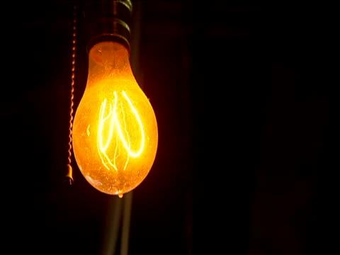 vidéos et rushes de antique light bulb filament glowing orange. focus-pull at end - vigilance