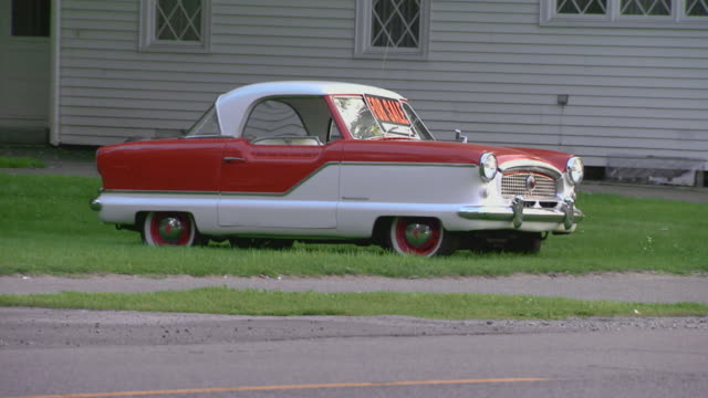 antique red and white car (nash metropolitan) for sale - classic car stock videos and b-roll footage
