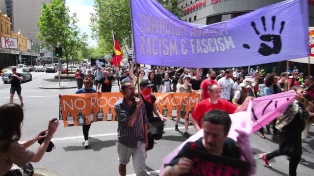 antiracism protesters gather to counter protest against a donald trump victory rally outside state parliament on november 20 2016 in melbourne... - political rally stock videos & royalty-free footage