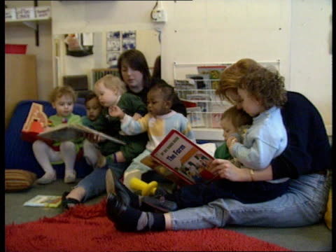 children in playgroup looking at books - nursery school building stock videos and b-roll footage