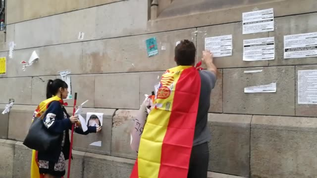 vídeos y material grabado en eventos de stock de antireferendum protesters wrapped in the spanish flags remove proindependence banners put up on walls and throw them into garbage cans during the... - 2017