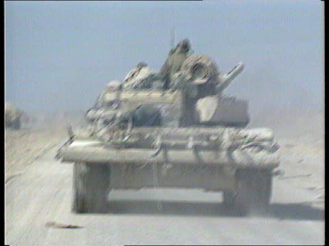 anti-saddam hussein unrest; basra: iraqi t-72 tanks along road; bv ditto wrecked buildings iraqi army manning fortifications shown; smoke on horizon; - basra video stock e b–roll