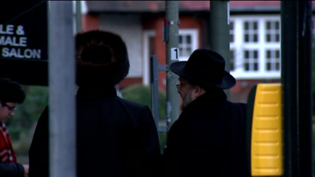stockvideo's en b-roll-footage met antisemitic attacks reach record levels golders green back view orthodox jews along on street back view man wearing skull cap along - orthodox jodendom