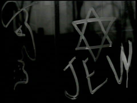 AntiSemitism NO soldier writing 'Jew' under Star of David on window Female male standing by tree wearing Star of David patch Window sign 'No Jews...