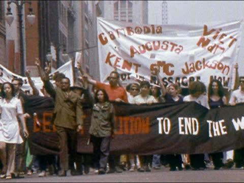 stockvideo's en b-roll-footage met 1970 antivietnam war demonstrators carrying banners in peace march down street - vredesteken handgebaar