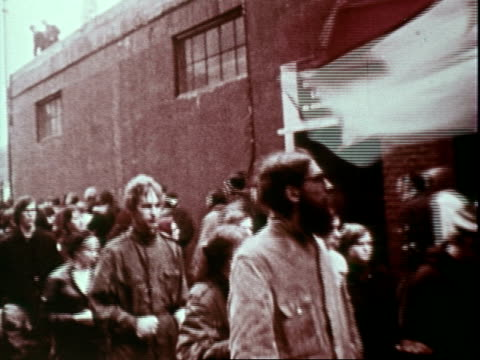 anti-war demonstrators marching toward fort dix, new jersey, with banners and placards and chants and pumped fists, only to be turned away by tear... - vietnam war stock videos & royalty-free footage