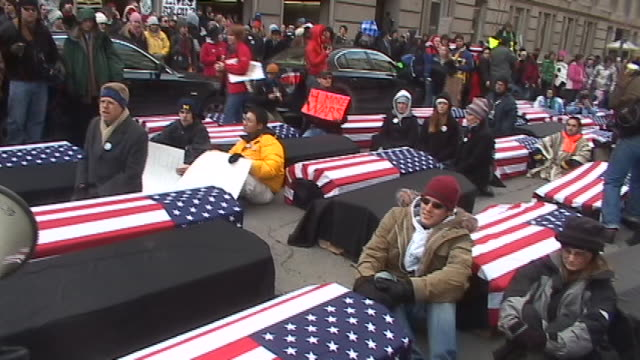 vídeos de stock, filmes e b-roll de antiwar protesters block a street with card board boxes covered with the american flag to symbolize the american war dead while protesting against... - 2005