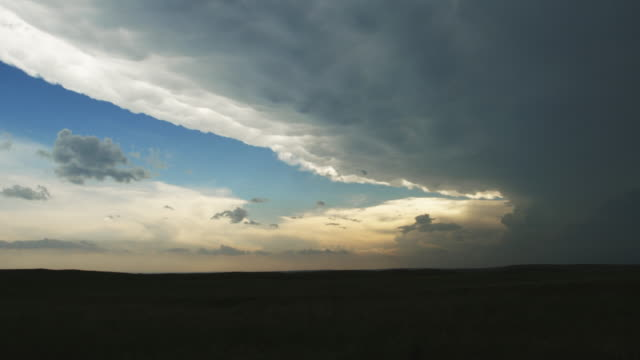 Anvil spreading out and away from a supercell thunderstorm by faster jet stream winds aloft over a prairie landscape, time lapse