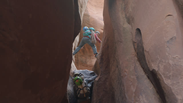 Anxious dog looks up as young men climb narrow slot canyon in Moab.