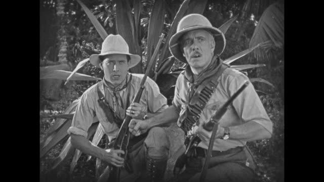 1925 Anxious explorers watch as stop motion dinosaur destroys tree bridge