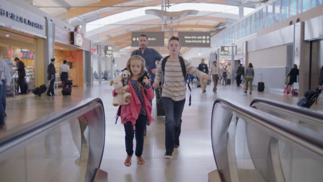 anxious family of four runs along moving walkway in airport terminal towards gate. - dringlichkeit stock-videos und b-roll-filmmaterial