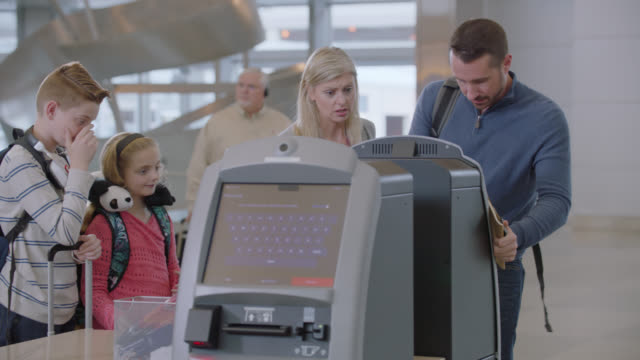 vidéos et rushes de anxious family of four waits in line then hurriedly checks in at kiosk in airport terminal. - stress