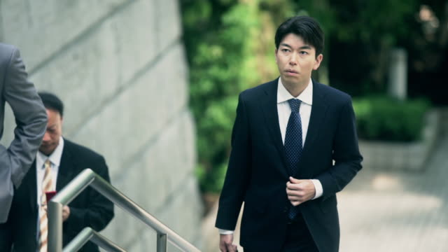 anxious looking businessman climbing stairs - 男商人 個影片檔及 b 捲影像