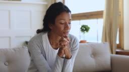Anxious thoughtful african woman on sofa looking away feel depressed