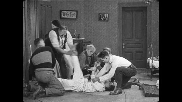 1922 Anxious woman calls in men to inspect a sleeping man (Buster Keaton) who won't wake up