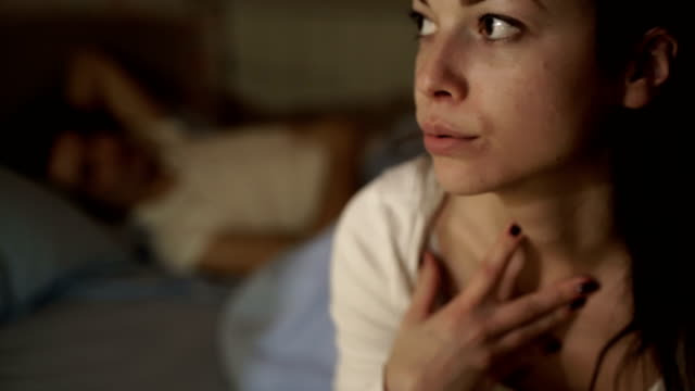 anxious woman thinking in her bed next to her sleeping partner - physical pressure stock videos & royalty-free footage