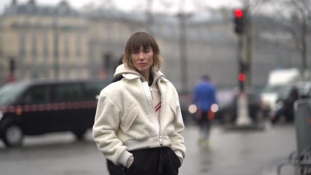 Anya Ziourova wears a white fluffy bomber jacket black pants outside Balmain during Paris Fashion Week Womenswear Fall/Winter 2018/2019 on March 2...