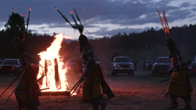 apache men move around fire during dusk, wide shot - native american reservation stock videos & royalty-free footage