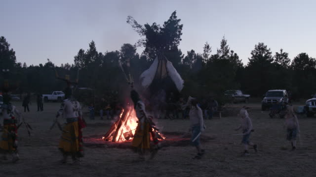 apache men run around fire at dusk during sunrise ceremony, wide shot - native american reservation stock videos & royalty-free footage