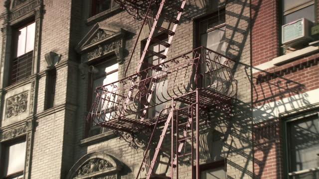 cu zo ms apartment building with fire escape in chinatown / new york city, new york, usa - 非常階段点の映像素材/bロール