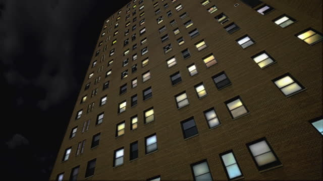 T/L, MS, LA, Apartment building with lights turning off throughout building / crescent moon passes in sky