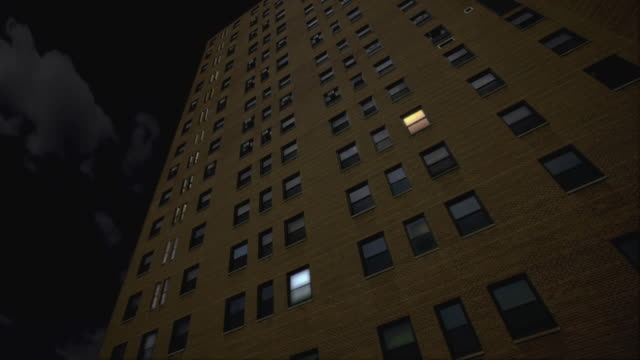 t/l, ms, la apartment building with lights turning on throughout building - luminosità video stock e b–roll