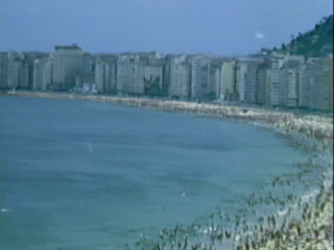 pan apartment buildings lining beach covered with people / rio de janeiro, brazil - lateinamerika stock-videos und b-roll-filmmaterial