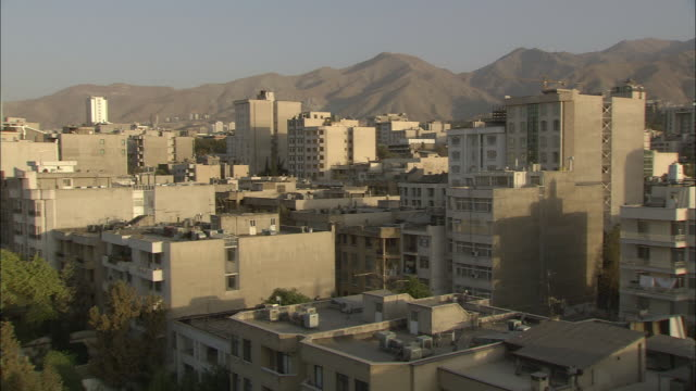 WS PAN Apartment buildings with mountain range in background at sunset / Teheran, Iran