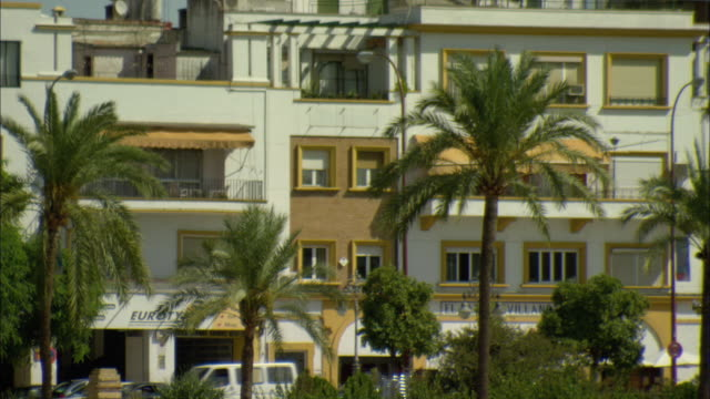 ms apartment buildings with palms in foreground / seville, andalusia, spain - awning stock videos and b-roll footage