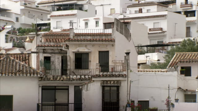 Apartment buildings with tile roofs cover a hillside in the village of Mijas, Spain.