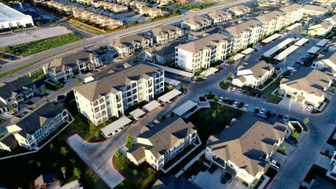 stockvideo's en b-roll-footage met appartement complex nieuwbouwproject luchtfoto drone weergave bij zonsondergang - ingewikkeldheid