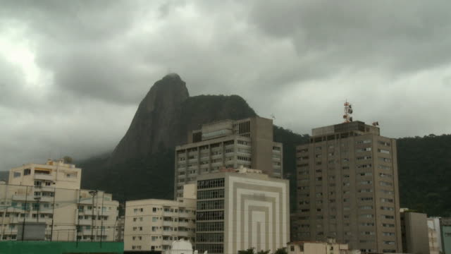 vídeos de stock, filmes e b-roll de ms, apartments buildings with corcovado mountain covered with clouds in background, rio de janeiro, brazil - overcast