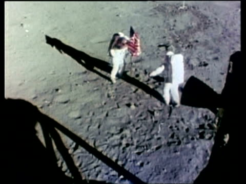 vídeos de stock e filmes b-roll de apollo 11 astronauts, buzz aldrin and neil armstrong, putting up the american flag, high angle, moon - lua