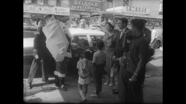 ext apollo theater in harlem / santa climbs out of a car with sack of toys / row of african american boys in military type uniforms shake hands with... - harlem stock videos & royalty-free footage