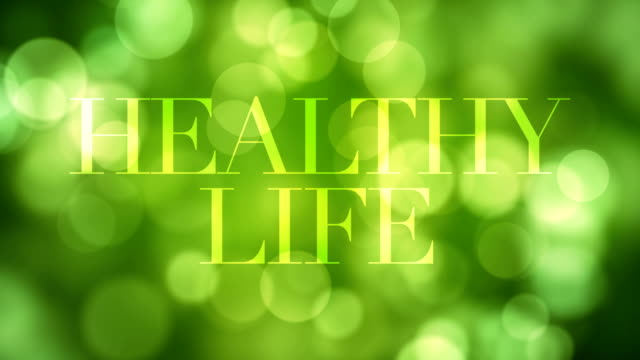 appearing 'healthy life' text and dissolving after a while with moving green glitter lights, defocused light reflections on loopable green bokeh background. healthy life, spring, forest concept video - dissolving stock videos and b-roll footage