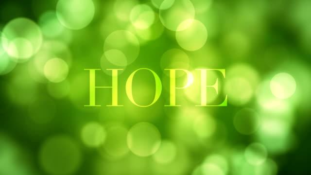 vidéos et rushes de apparaissant le texte «l'espoir» et la dissolution après un certain temps avec le déplacement des feux de paillettes vert, les reflets lumineux défocalisés sur bouclables vert bokeh fond. vie saine, printemps, forêt, vidéo concept illusoire - fondu de fermeture