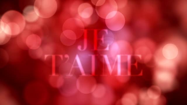 """apparendo testo """"je t'aime"""" e sciogliendo dopo un po 'con luci glitter rosse in movimento, riflessi di luce sfocati su sfondo bokeh rosso loopable. video loop loop able amore, amore e passione. - dissolvenza in apertura video stock e b–roll"""