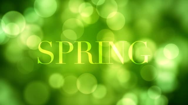 'spring' text erscheinen und nach einer weile mit moving-lights grün glitter auflösen, grünen defokussierten lichtreflexionen auf endlos wiederholbar bokeh hintergrund. gesundes leben, frisch, wald, saison konzeptvideo - abblenden stock-videos und b-roll-filmmaterial