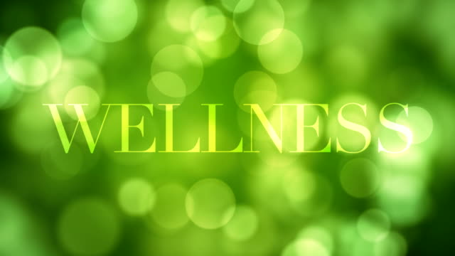 appearing 'wellness' text and dissolving after a while with moving green glitter lights, defocused light reflections on loopable green bokeh background. healthy life, spring, forest concept video - dissolving stock videos & royalty-free footage