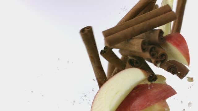 apple and cinnamon sticks collide mid-air - cinnamon stock videos & royalty-free footage