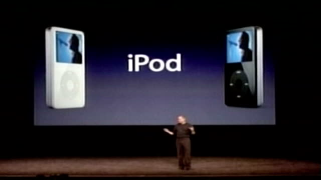 apple corps loses to apple computers in court battle tx unidentified man on stage demonstrating ipods - mp3プレイヤー点の映像素材/bロール