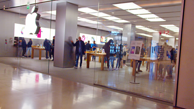 apple shop at paris financial district. indoors. apple big illuminated sign. many customers. crowd. - apple fruit stock videos & royalty-free footage
