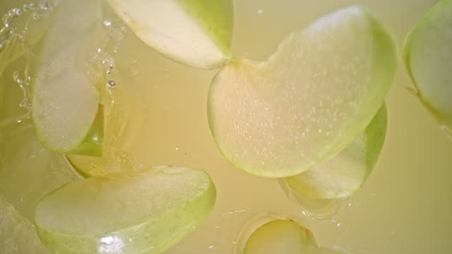 slo mo ld apple wedges falling into apple juice - apple fruit stock videos & royalty-free footage