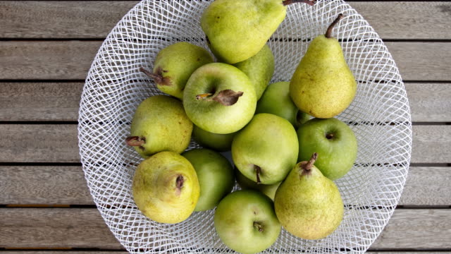 apples and pears in decorative bowl on wooden table - fruit bowl stock videos & royalty-free footage