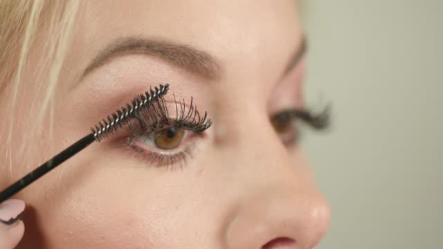 Applying black mascara with applicator