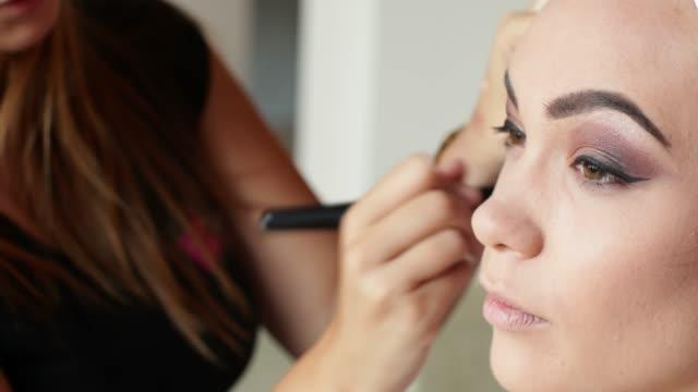vídeos de stock, filmes e b-roll de aplicar o blush com pincel de maquiagem no rosto do modelo - blush