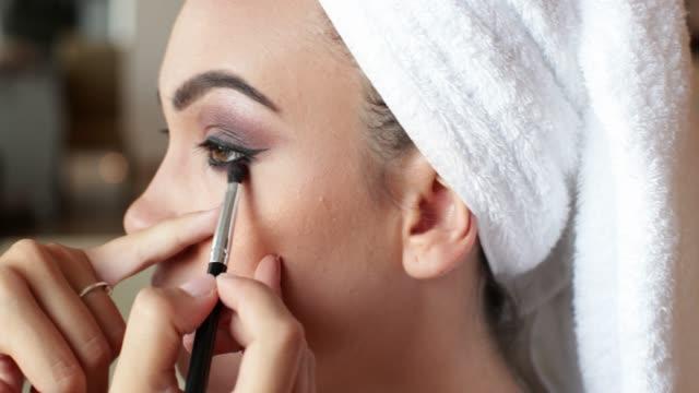 vídeos y material grabado en eventos de stock de aplicar sombra de ojos con pincel en la cara del modelo de concurso de belleza - concurso de belleza