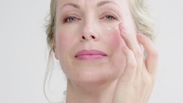 vídeos de stock e filmes b-roll de applying face cream - aplicar