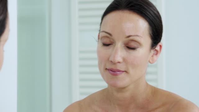 applying face cream - medelålders kvinnor bildbanksvideor och videomaterial från bakom kulisserna