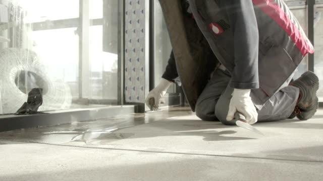 applicazione di resina liquida su pavimento in cemento con cazzuola - sigillante video stock e b–roll